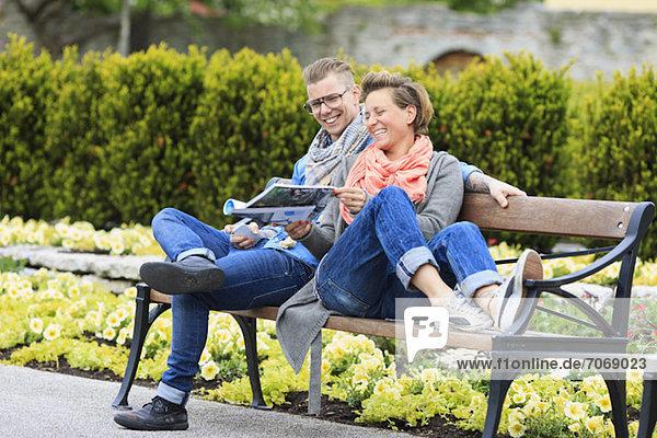 Fröhliches Paar  das auf der Parkbank sitzt und etwas aus dem Magazin genießt.