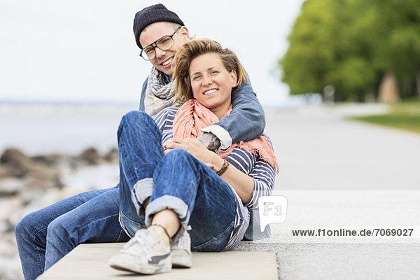 Porträt eines glücklichen Paares am Rande einer Mauer