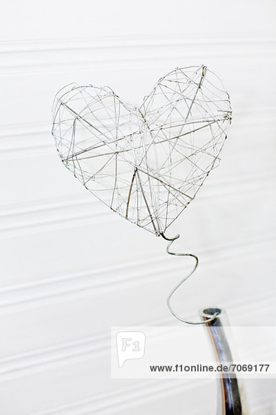 Nahaufnahme der drahtbildenden Herzform auf weißem Hintergrund