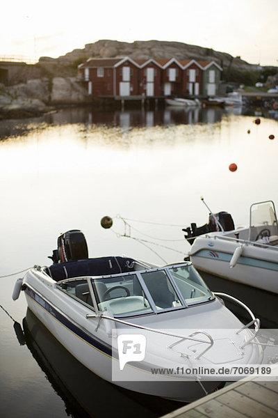 Verankerte Schnellboote im Hafen mit Kabinen im Hintergrund