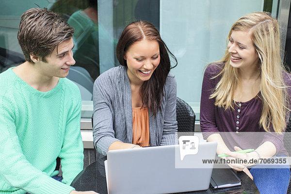 Drei glückliche Freunde mit Laptop am Couchtisch