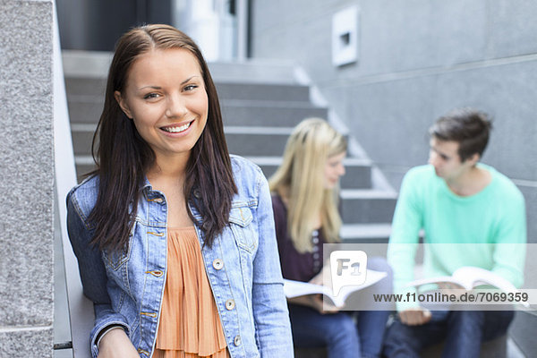 Portrait of a happy female student with friends studying on steps in the background