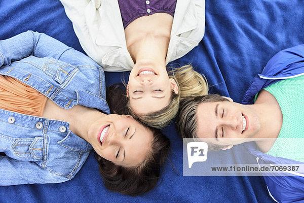 Direkt über der Aufnahme von drei glücklichen Freunden mit geschlossenen Augen auf blauem Tuch liegend