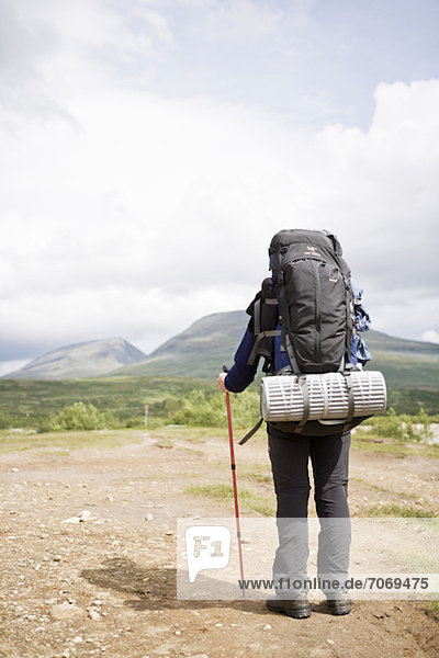 Rückansicht einer Frau mit Rucksack und Wanderstock
