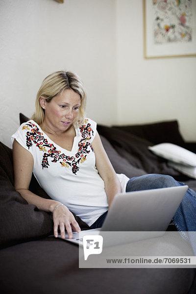 Mittlere erwachsene Frau schaut auf Laptop auf Sofa