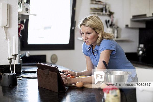 Frau sucht Rezepte in digitaler Tablette in der Küche