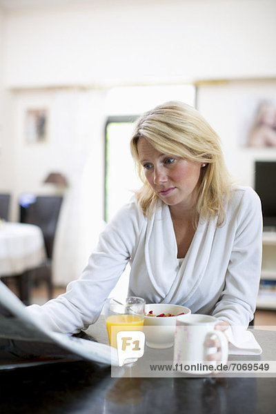 Mittlere erwachsene Frau im Bademantel liest Zeitung beim Frühstücken