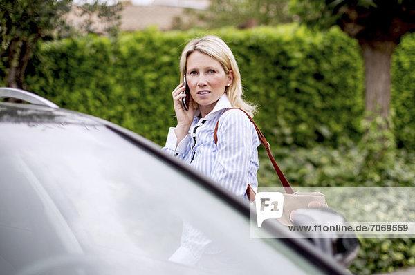 Mittlere erwachsene Frau  die mit dem Auto telefoniert.