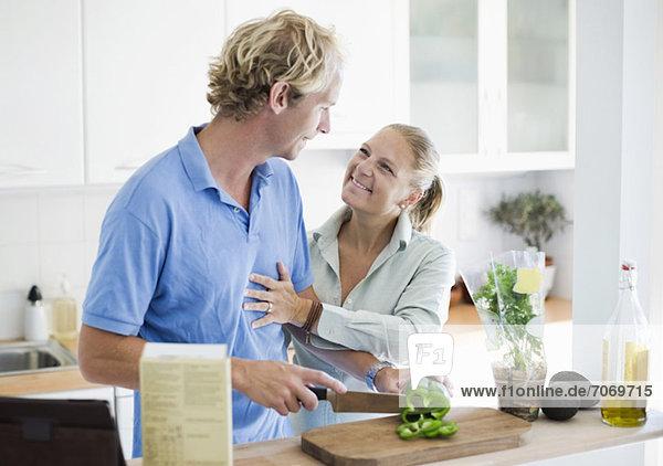 Glücklicher Mann  der Gemüse schneidet  während seine Frau ihn in der Küche umarmt.