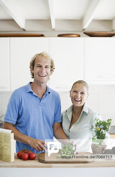 Porträt eines glücklichen Paares in der Küche beim Schneiden von Gemüse