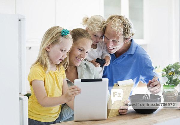 Kleines Mädchen mit Eltern mit digitalem Tablett für das Rezept in der Küche