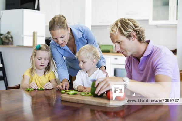 Paar mit Töchtern beim Gemüsehacken in der Küche