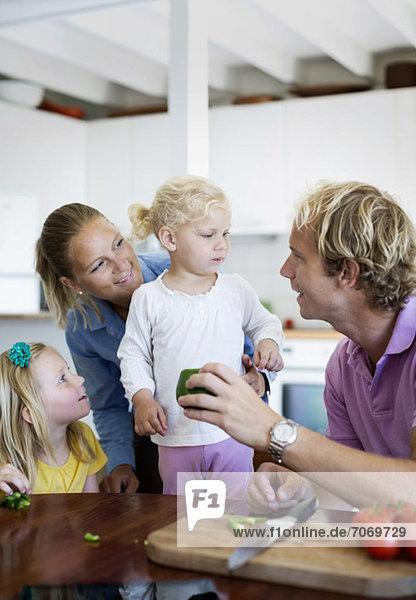 Paar mit Töchtern in der heimischen Küche