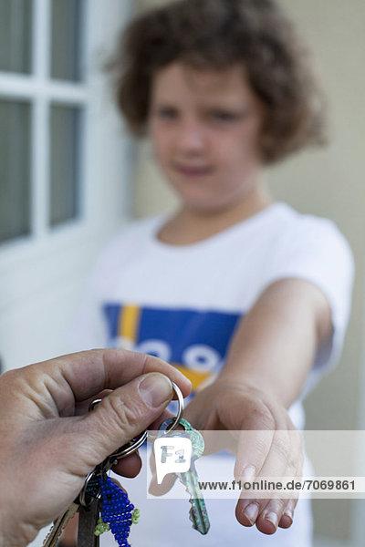 Abgeschnittenes Bild von der Hand des Mannes  der dem kleinen Mädchen die Schlüssel übergibt
