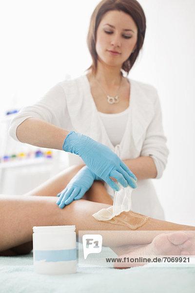 Junge Kosmetikerin  die eine Zuckerkur für eine erwachsene Frau im Beauty-Spa macht