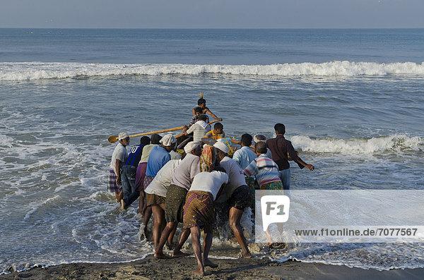 Fischer schieben ein Boot ins Meer  an der K¸ste in der Nähe von Varkala  Indien  Asien