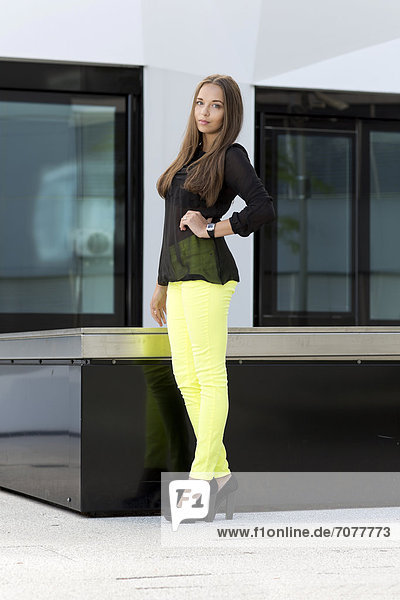 Young woman wearing a black top  bright yellow trousers and high black shoes