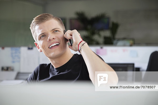 Thoughtful young man looking away while using cell phone at office