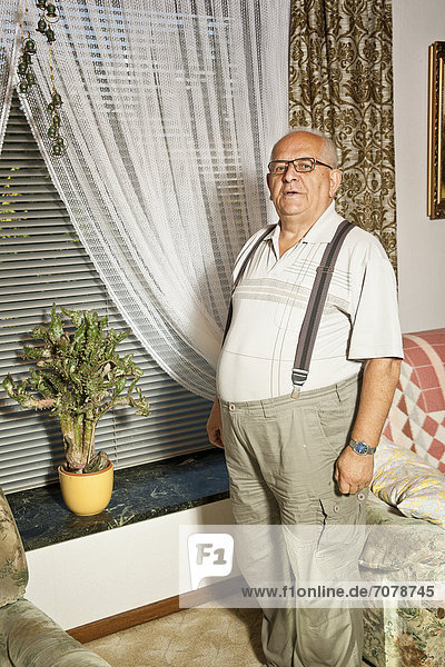 Retired man standing in front of a cactus on a window sill