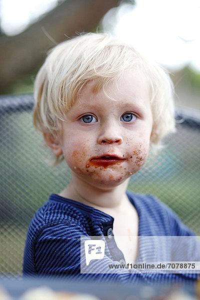Kleiner Junge mit schokoladenverschmiertem Mund