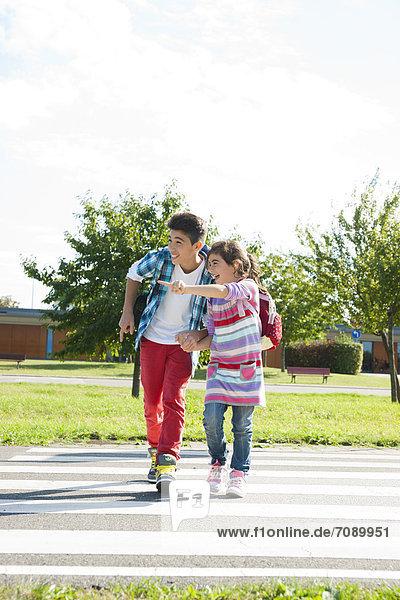 Mädchen und Junge überqueren die Straße an einem Zebrastreifen auf einem Verkehrsübungsplatz
