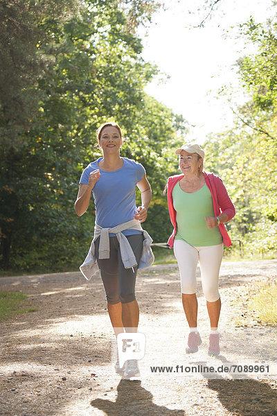 Zwei Frauen joggen auf einem Waldweg