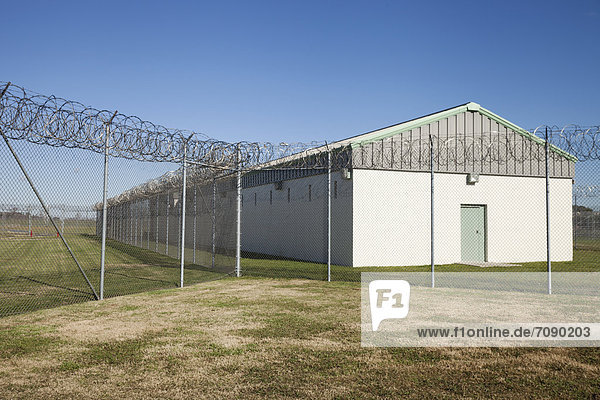 A residential unit  wing or dormitory building for prisoners at aCorrectional Facility. Fence with razor wire.
