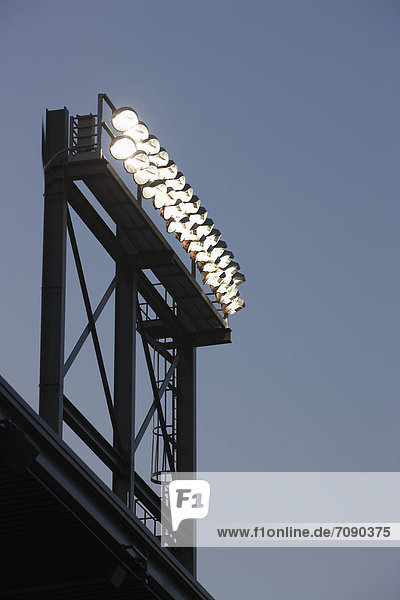 A tall lighting gantry or tower with strong powerful floodlights  over a sports area or stadium.