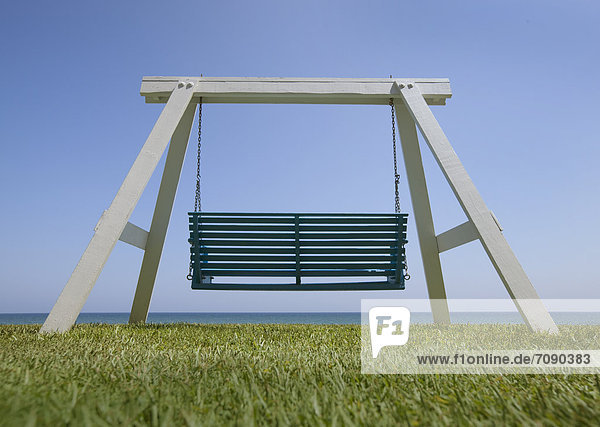 A wooden beach swing with a green painted seat. A good view of the sea.