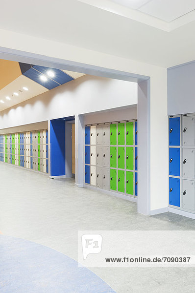 Corridor of a modern secondary school  with rows of lockers in green blue and white.