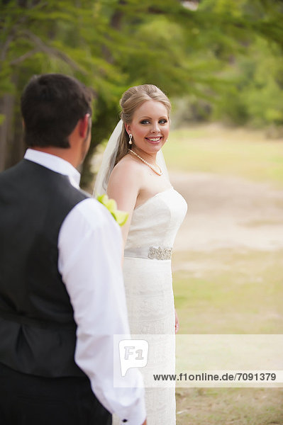 USA  Texas  Bride and groom looking at each other  smiling