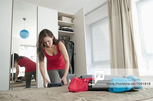 Junge Frau beim Kofferpacken