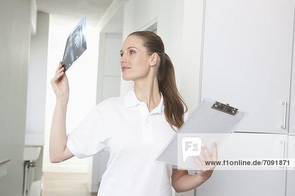 Germany  Dentist looking at dental x-rays