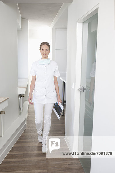 Germany  Dentist walking with clip board