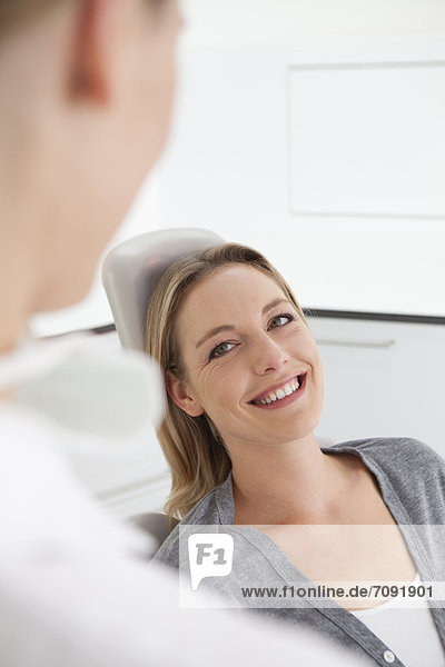Germany  Mid adult woman in dentist chair  smiling