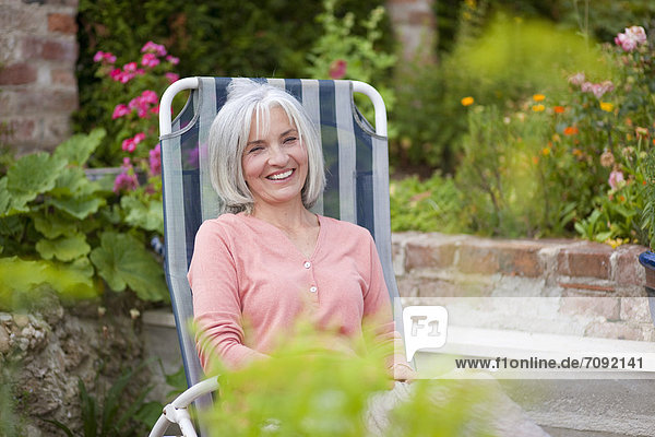 Mature woman sitting in lawn chair