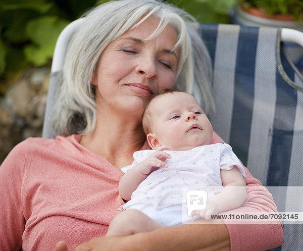 Frau mit Enkelkind entspannt im Liegestuhl