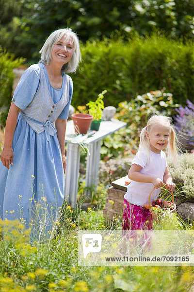 Mature woman with girl in garden