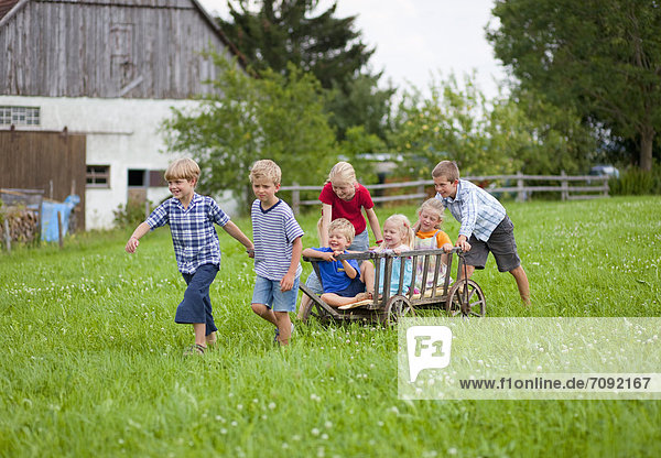Germany  Bavaria  Group of children playing with hand cart in front of farmhouse