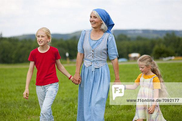 Deutschland  Bayern  Großmutter mit Kindern auf der Wiese