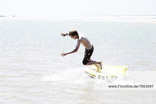 Frankreich  Junge beim Surfen an der Atlantikküste