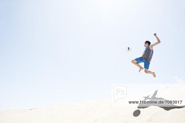 Frankreich  Teenager Junge springt auf Sanddüne nach Fußball