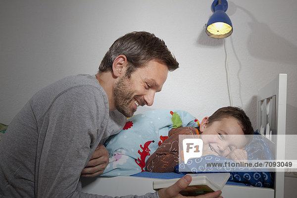 Deutschland  Berlin  Vater liest Buch im Schlaf des Sohnes