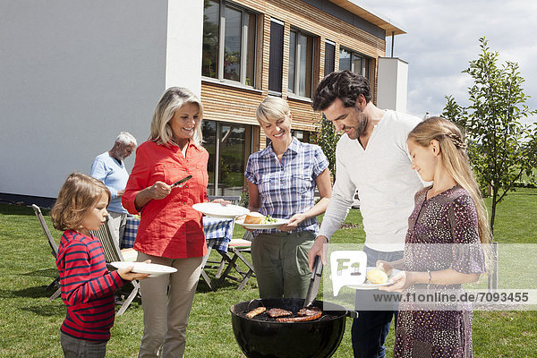 Germany  Bavaria  Nuremberg  Family standing around barbecue in garden