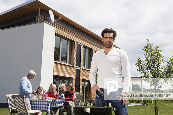 Man cooking barbecue,  family sitting in garden