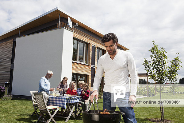 Man cooking barbecue  family sitting in garden