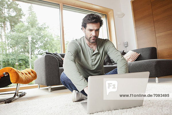 Mature man using laptop in living room
