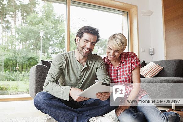 Deutschland  Bayern  Nürnberg  Ehepaar mit digitalem Tablett im Wohnzimmer
