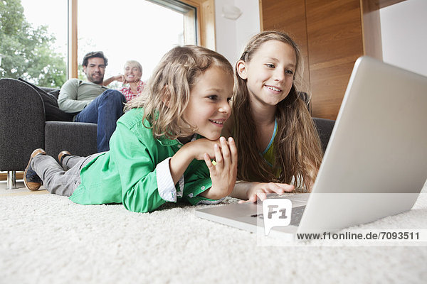 Girl and boy using laptop in living room