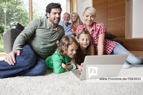 Deutschland  Bayern  Nürnberg  Familie mit Laptop im Wohnzimmer